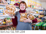Купить «Portrait of smiling mature woman buying bakery products», фото № 32181234, снято 15 декабря 2017 г. (c) Яков Филимонов / Фотобанк Лори
