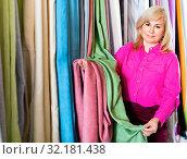 Купить «Positive mature woman seller showing curtain in the curtains shop», фото № 32181438, снято 17 января 2018 г. (c) Яков Филимонов / Фотобанк Лори