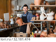 Smiling man artisan having ceramics in hands. Стоковое фото, фотограф Яков Филимонов / Фотобанк Лори