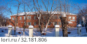 A red brick building with large cage windows behind trees in a snowy courtyard (2019 год). Редакционное фото, фотограф Владимир Аликин / Фотобанк Лори