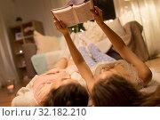 Купить «happy female friends reading book at home», фото № 32182210, снято 21 января 2018 г. (c) Syda Productions / Фотобанк Лори