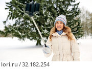 Купить «woman taking picture by selfie stick in winter», фото № 32182254, снято 20 января 2019 г. (c) Syda Productions / Фотобанк Лори