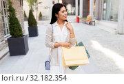 Купить «asian woman with shopping bags walking in city», фото № 32182354, снято 13 июля 2019 г. (c) Syda Productions / Фотобанк Лори