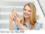 Купить «teenage girl taking selfie by smartphone on stairs», фото № 32182498, снято 29 марта 2014 г. (c) Syda Productions / Фотобанк Лори