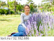 Купить «young woman and lavender flowers at summer garden», фото № 32182686, снято 12 июля 2019 г. (c) Syda Productions / Фотобанк Лори