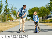 Купить «father and little son riding scooters in city», фото № 32182770, снято 1 августа 2019 г. (c) Syda Productions / Фотобанк Лори