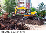 Купить «Yellow excavator digging a trench near the apartment building», фото № 32184546, снято 25 мая 2017 г. (c) FotograFF / Фотобанк Лори