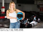Купить «Pretty woman with helmet standing near cars», фото № 32185098, снято 22 октября 2019 г. (c) Яков Филимонов / Фотобанк Лори
