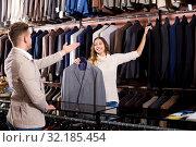 Купить «Female seller demonstrating numerous suits», фото № 32185454, снято 21 февраля 2020 г. (c) Яков Филимонов / Фотобанк Лори
