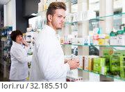 Купить «Pharmaceutist working in chemist shop», фото № 32185510, снято 21 октября 2016 г. (c) Яков Филимонов / Фотобанк Лори