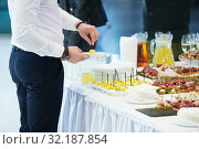 Catering service. man take snack from food court table at event. Стоковое фото, фотограф Дмитрий Калиновский / Фотобанк Лори