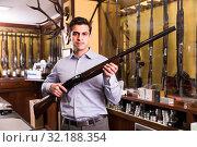 Smiling male hunter choosing shotgun in store. Стоковое фото, фотограф Яков Филимонов / Фотобанк Лори