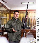 Confident hunter male wearing windbreaker in hunting shop with rifle in hands. Стоковое фото, фотограф Яков Филимонов / Фотобанк Лори