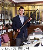 Salesman in hunting store demonstrating shotgun. Стоковое фото, фотограф Яков Филимонов / Фотобанк Лори