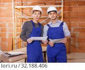 Купить «Builders holding papers with plan», фото № 32188406, снято 12 февраля 2019 г. (c) Яков Филимонов / Фотобанк Лори