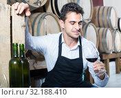 Купить «male seller holding glass on wine in cellar», фото № 32188410, снято 22 сентября 2019 г. (c) Яков Филимонов / Фотобанк Лори