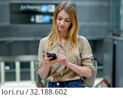 Купить «Nice woman with long hair is writing a message on a mobile phone in the lobby of the subway», фото № 32188602, снято 31 марта 2019 г. (c) Яков Филимонов / Фотобанк Лори