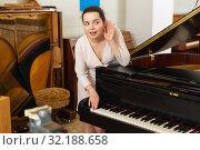 Купить «Saleswoman assistant in piano music store», фото № 32188658, снято 16 апреля 2019 г. (c) Яков Филимонов / Фотобанк Лори