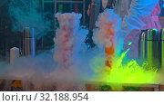 Купить «A scientist performing a show with liquid nitrogen in the flasks - plenty of smoke in neon lights», видеоролик № 32188954, снято 22 сентября 2019 г. (c) Константин Шишкин / Фотобанк Лори
