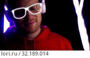 Купить «man in headphones over neon lights of night club», видеоролик № 32189014, снято 22 октября 2019 г. (c) Syda Productions / Фотобанк Лори