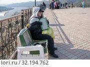 Купить «Мужчина зарабатывает деньги играя на гармони, сидя на скамейке на смотровой площадке над рекой Енисей», фото № 32194762, снято 6 апреля 2019 г. (c) Светлана Попова / Фотобанк Лори