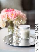 Купить «aroma reed diffuser, candle and flowers on table», фото № 32198666, снято 11 апреля 2019 г. (c) Syda Productions / Фотобанк Лори