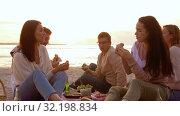 happy friends eating sandwiches at picnic on beach. Стоковое видео, видеограф Syda Productions / Фотобанк Лори
