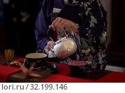 Купить «Женщина в кимоно наливает горячую воду из чайника в чашку с чаем во время традиционной японской чайной церемонии», фото № 32199146, снято 31 августа 2019 г. (c) Николай Винокуров / Фотобанк Лори