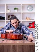Купить «Young handsome repairman repairing cello», фото № 32200050, снято 4 апреля 2019 г. (c) Elnur / Фотобанк Лори