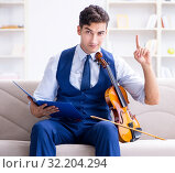 Купить «Young musician man practicing playing violin at home», фото № 32204294, снято 15 августа 2017 г. (c) Elnur / Фотобанк Лори