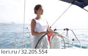 Купить «Young attractive woman standing at yacht wheel during luxury sea trip», видеоролик № 32205554, снято 30 июля 2019 г. (c) Яков Филимонов / Фотобанк Лори