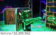Joyful teens aiming laser guns at other players during lasertag game in dark room. Стоковое видео, видеограф Яков Филимонов / Фотобанк Лори