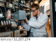 Купить «Scientist in glasses holds electrical device», фото № 32207274, снято 17 июня 2019 г. (c) Tryapitsyn Sergiy / Фотобанк Лори