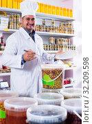 Купить «Shop staff standing near containers with olives in flavoured brine», фото № 32209598, снято 15 октября 2016 г. (c) Яков Филимонов / Фотобанк Лори