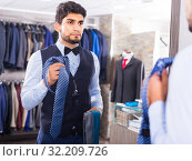 Male is picking up tie for waistcoat in front of the mirror. Стоковое фото, фотограф Яков Филимонов / Фотобанк Лори