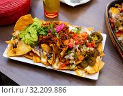 Купить «Corn chips nachos with meat, cheese, vegetables and guacamole», фото № 32209886, снято 3 апреля 2020 г. (c) Яков Филимонов / Фотобанк Лори