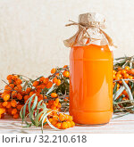 Vegetarian food, healthy nutrition, preserving the harvest of ripe juicy sea-buckthorn, preparing fresh healthy vitamin drink and healing broth. Jug with juice and branches of orange sea buckthorn. Стоковое фото, фотограф Светлана Евграфова / Фотобанк Лори
