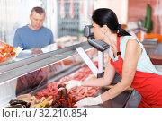 Купить «Young seller helping male choosing sausages», фото № 32210854, снято 22 июня 2018 г. (c) Яков Филимонов / Фотобанк Лори