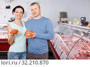 Купить «Positive couple customers posing with meat», фото № 32210870, снято 22 июня 2018 г. (c) Яков Филимонов / Фотобанк Лори