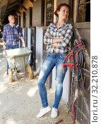 Купить «Mature positive female farmer standing near horse at stable», фото № 32210878, снято 4 июля 2018 г. (c) Яков Филимонов / Фотобанк Лори