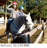 Купить «Woman and man in helmets training riding horse at farm at summer day», фото № 32210886, снято 4 июля 2018 г. (c) Яков Филимонов / Фотобанк Лори