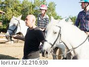 Купить «Positive mature couple with jockey learn to riding horse at farm», фото № 32210930, снято 12 декабря 2019 г. (c) Яков Филимонов / Фотобанк Лори