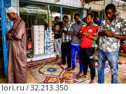 Muslims praying outside outside a shop in Ouagadougou, Burkina Faso. Стоковое фото, фотограф Philippe Lissac / Godong / age Fotostock / Фотобанк Лори