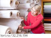Купить «Elderly woman choosing interesting fabric», фото № 32216194, снято 15 февраля 2017 г. (c) Яков Филимонов / Фотобанк Лори
