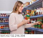 Купить «Female in shop holding pickle goods in grocery section», фото № 32216334, снято 11 апреля 2018 г. (c) Яков Филимонов / Фотобанк Лори