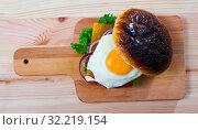 Купить «Hamburger with with fried egg, beef, onion, cheese and lettuce», фото № 32219154, снято 22 октября 2019 г. (c) Яков Филимонов / Фотобанк Лори