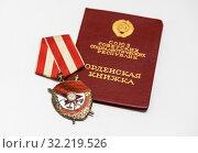 Купить «Орден Красного Знамени (орден «Красное знамя») лежит на орденской книжке», эксклюзивное фото № 32219526, снято 15 апреля 2019 г. (c) Игорь Низов / Фотобанк Лори