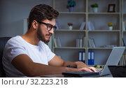 Купить «Young man staying late in office to do overtime work», фото № 32223218, снято 5 июля 2017 г. (c) Elnur / Фотобанк Лори