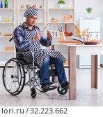 Купить «Disabled young man husband working in kitchen», фото № 32223662, снято 20 апреля 2017 г. (c) Elnur / Фотобанк Лори