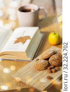Купить «oat cookies, almonds and book on table at home», фото № 32224702, снято 15 ноября 2017 г. (c) Syda Productions / Фотобанк Лори